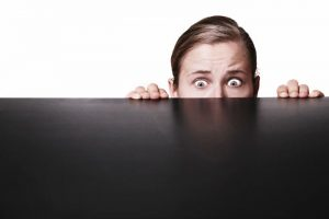 man hiding behind a desk