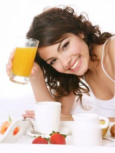 woman smiling and drinking orange juice